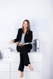 有黏合剂的愉快的女实业家坐柜台 免版税库存照片