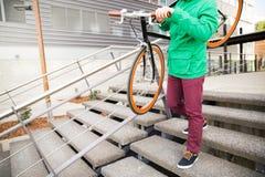 有去固定的齿轮的自行车的人楼下 库存图片