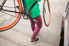 有去固定的齿轮的自行车的人楼下 库存照片