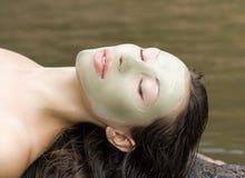 有黏土面部面具的妇女在秀丽温泉(室外) 图库摄影