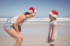 有戴圣诞老人帽子的女儿的快乐的妇女在海滩 免版税库存图片