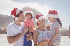 有戴圣诞老人帽子的父母的愉快的孩子在海滩 库存照片