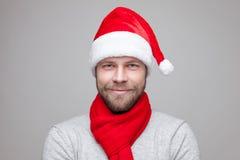 有戴圣诞节帽子的胡子的英俊的人 免版税库存照片