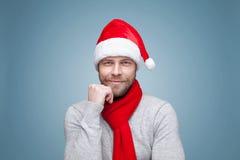 有戴圣诞节帽子的胡子的英俊的人 库存照片