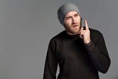 有戴在灰色背景的胡子的一个年轻人一个帽子 免版税库存照片