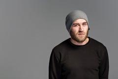 有戴在灰色背景的胡子的一个年轻人一个帽子 免版税图库摄影