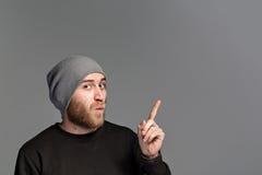 有戴在灰色背景的胡子的一个年轻人一个帽子 库存照片