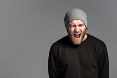 有戴在灰色背景的胡子的一个年轻人一个帽子 库存图片