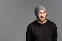 有戴在灰色背景的胡子的一个年轻人一个帽子 免版税库存图片