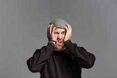 有戴在灰色背景的胡子的一个年轻人一个帽子 图库摄影