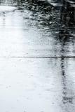 有水坑的湿街道路在多雨天气期间 库存图片
