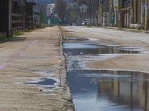 有水坑的老路由路旁 免版税库存照片