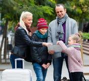 有读城市地图的孩子的家庭 免版税图库摄影