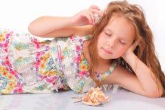 有贝壳和海星的镇静小女孩 库存图片