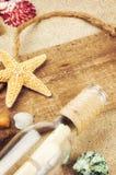 有贝壳和瓶的老木板 库存照片