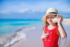 有贝壳的小逗人喜爱的女孩在热带海滩的手上 免版税图库摄影