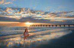 有贝壳的愉快的微笑的女孩在日出的美丽的海滩 库存照片