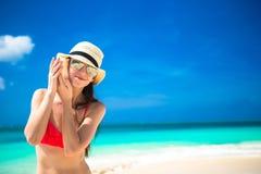 有贝壳的美丽的女孩在热带海滩的手上 库存照片