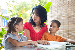 有年轻女儿和儿子读书的亚裔母亲 免版税图库摄影