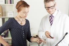 有年轻女性耐心妇女的医生 免版税库存照片