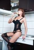 有黑女用贴身内衣裤的喝酒的可爱的性感的红色头发女性和长袜在一个现代厨房里。肉欲的红头发人画象  免版税库存图片
