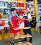 有钻子工具箱的推销员在五金店 免版税库存图片