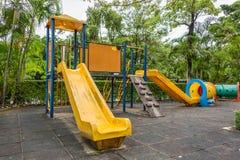 有滑子的儿童操场和隧道残余物在公园 免版税图库摄影