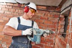 有钻子穿孔器的建筑工人 库存图片
