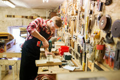 有钻子钻板条的木匠在车间 免版税库存图片