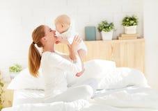 有婴孩使用的愉快的家庭母亲和拥抱在床上 免版税库存图片