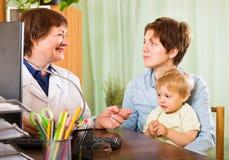 有婴孩听的儿科医生医生的母亲 库存照片