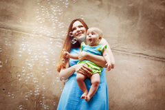 有婴孩吹的泡影的美丽的年轻母亲 图库摄影