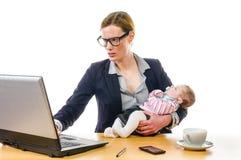 有婴孩和个人计算机的女实业家 免版税库存图片