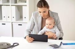 有婴孩和片剂个人计算机的女实业家在办公室 免版税库存图片
