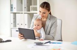 有婴孩和片剂个人计算机的女实业家在办公室 库存照片