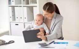 有婴孩和片剂个人计算机的女实业家在办公室 免版税图库摄影