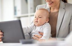 有婴孩和片剂个人计算机的女实业家在办公室 库存图片