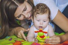 有婴孩戏剧五颜六色的玩具的妇女 库存图片