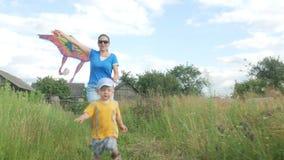 有婴孩的一个年轻母亲在夏天发射在一个绿色领域的空气风筝 母亲不很好做 非常愉快的儿子 股票视频
