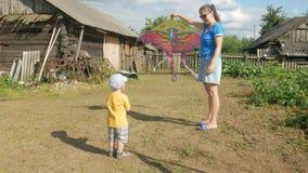 有婴孩的一个年轻母亲在夏天发射在一个绿色领域的空气风筝 母亲不很好做 非常愉快的儿子 影视素材