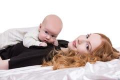 有婴孩的可爱的红发妇女胸口的 库存照片
