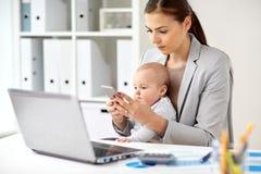 有婴孩的女实业家和智能手机在办公室 免版税库存照片