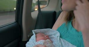 有婴孩的妇女乘坐汽车的胳膊的 股票视频