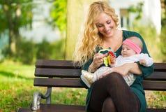 有婴孩的妈妈在公园 免版税库存照片