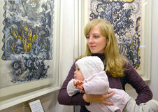 有婴孩的少妇考虑一张图片在exhibitio 库存照片