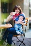 有婴孩的愉快的年轻母亲咖啡馆的 库存图片