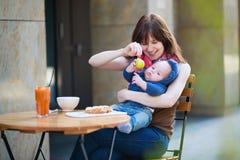 有婴孩的愉快的年轻母亲咖啡馆的 免版税库存照片