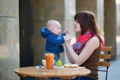 有婴孩的愉快的年轻母亲咖啡馆的 库存照片