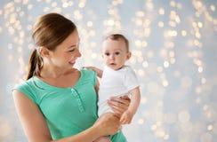 有婴孩的愉快的年轻母亲在假日点燃 免版税图库摄影