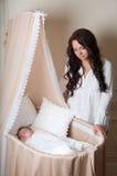 有婴孩的母亲。在床,摇篮上的婴孩睡眠 免版税图库摄影